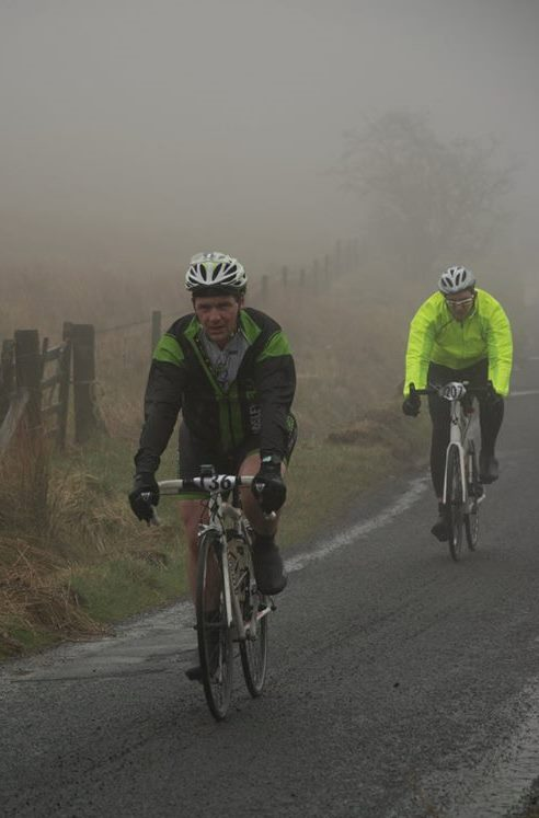 Cyclists emerge from the mist
